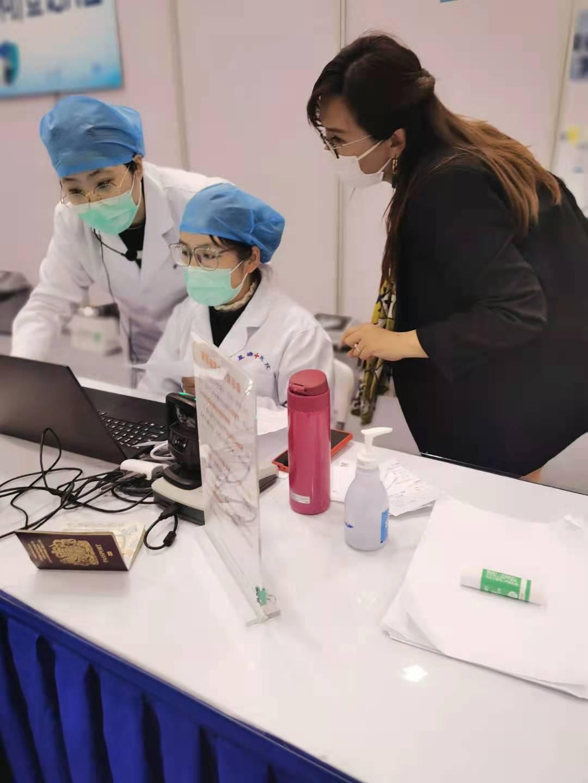 苏州德威外籍人员子女学校行政副校长Ann Ng(右)  与医护人员交谈