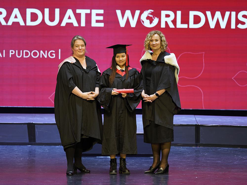 校长, Caroline Taylor女士 (右) 和中学部校长, Alison Derbyshire女士 (左) 和毕业生Vanessa T (中) 在毕业典礼的舞台上