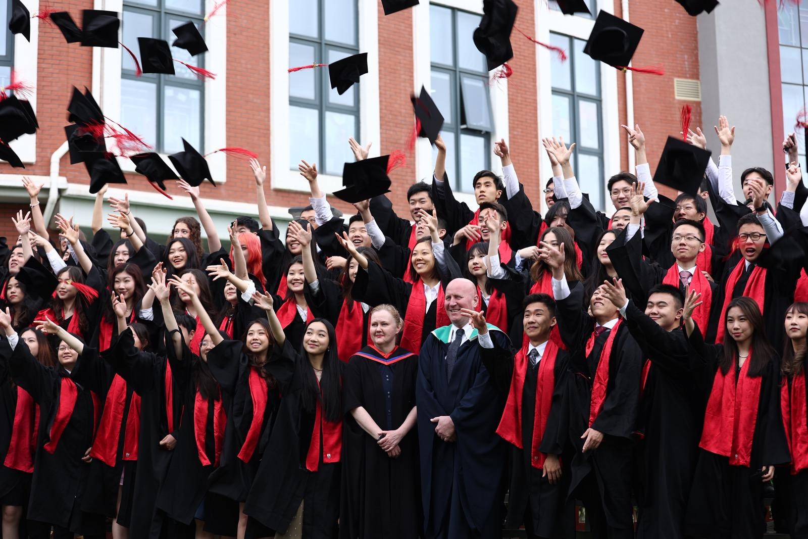 DCB graduation photo - hat throwing