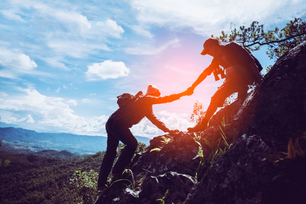 two-friends-helping-each-other-with-teamwork-trying-reach-top-mountains-2379-1741