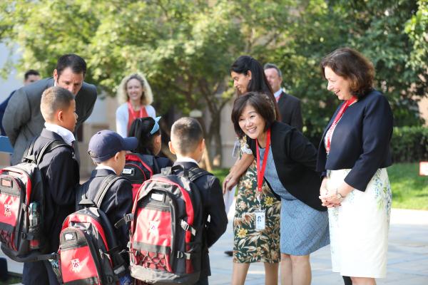 北京德闳学校的校长在门口迎接报到新生